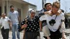 Ein Mann trägt im Libanon eine alte, kranke Frau auf dem Rücken. Ein andere alte Frau mit Kopftuch folgt den beiden.