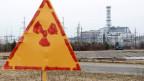 Kernkraftwerk in Tschernobyl mit Atomwarntafel im Vordergrund.