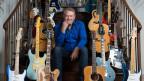 Glen Campbell posiert mit vielen Gitarren auf der Treppe.