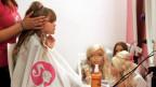 Ein kleines Mädchen wird geschminkt.