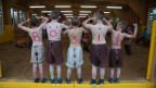 Jungs stehen mit nacktem Oberkörper in einem Festerrahmen. Auf ihrem Rücken steht «bösi Buebe»
