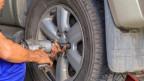 Ein Automechaniker knieend neben einem Auto. Er wechselt mit einem Schraubstock die Reifen.