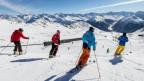Skifahrer fahren mit Skilehrer den Hang hinunter.