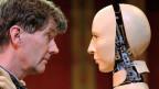 Mensch und Roboter schauen sich an.