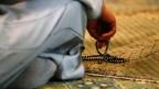 Symbolbild: Ein Mann in einer Moschee hält eine Gebetskette.