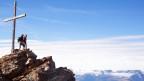 Zwei Wanderer stehen auf einer Bergspitze, neben ihnen das Gipfelkreuz.