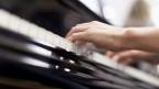 Zwei Hände auf der Tastatur eines Klaviers.