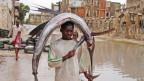 Ein Jugendlicher trägt in Mogadischu einen Fisch zum Markt.