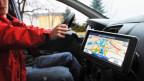 Symbolbild: Fahrkabine eines Autos mit Navigationsgerät.