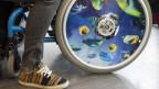 Mann im Rollstuhl mit bunten Fischen auf einem Rad