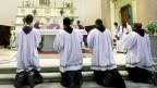 Vier katholische Priester Knien vor einem Altar.