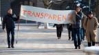 Zwei Personen gehen mit einem Transparenz-Transparent durch die Strasse.