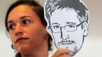 Eine Frau hält eine Zeichnung von Edward Snowden.