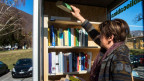 Eine Frau nimmt ein Buch aus einer mobilen Bibliothek.