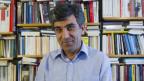 Yusuf Yesilöz vor einem Büchergestell.