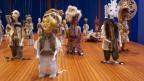 Marionetten in einem Raum.