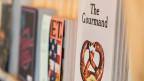 """Zeitschriften in einem Regal. Beim vordersten Heft ist der Titel """"The Gourmand"""" zu lesen, die anderen sind unscharf."""