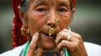 Eine Frau in Nepal spielt eine Maultrommel