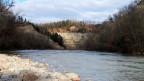 Eine Felswand mit Wald obendrauf, davor ein Fluss mit steinigem Ufer.