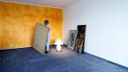Symbolbild: Eine Frau trägt Bilder aus einer fast leeren Wohnung.