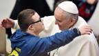 Papst Benedikt umarmt einen Jugendlichen mit Behinderung.