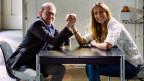 Der Komiker Viktor Giacobbo und die Schauspielerin Melanie Winiger beim Armdrücken am Tisch.