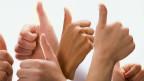 Viele Hände zeigen mit dem Daumen nach oben