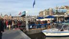 Warteschlangen, wo man hinschaut. Hier an der Bootsanlegestelle vor dem Hauptbahnhof, von wo aus die Touristen Rundfahrten durch Amsterdams Grachten unternehmen.