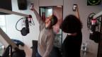 Zwei Menschen stehen mit dem Rücken zur Kamera und dem Handy in der Hand im Radiostudio-