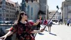 Asiatische Touristen machen auf der Münsterbrücke in Zürich Selfies.