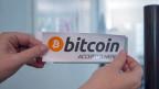 Ein Bitcoin-Kleber an der Tür zur Zuger Stadtverwaltung anlässlich der ersten Bitcoin Transaktion in einer Stadtverwaltung im Juli 2016 in der Stadtverwaltung der Stadt Zug.