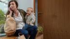 Symbolbild: Eine Mutter mit Kind erledigt einen geschäftlichen Telefonanruf.