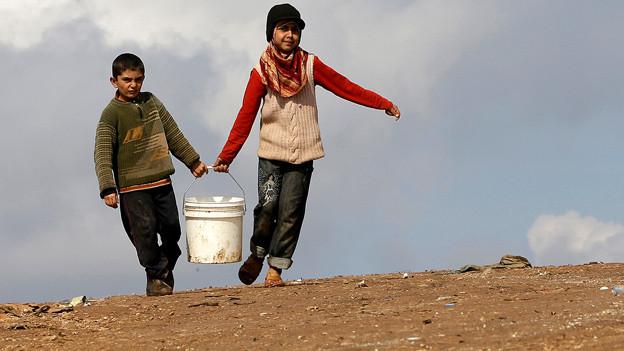 Flüchtlingskinder tragen einen Wassereimer im Atmeh Flüchtlingslager im Norden Syriens.