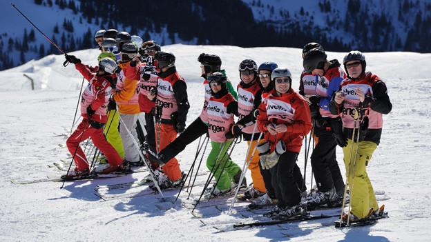 Freiwillige Helfer auf Skiern auf der Piste.