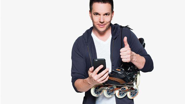 Sven Epiney posiert mit Inline-Skates und Handy.