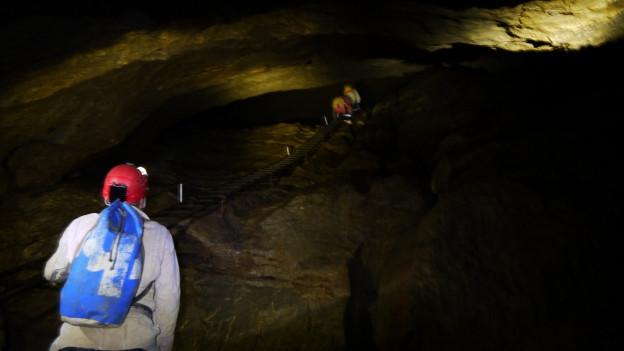 Ein Höhlenforscher im taschenlampenbeleuchteten Dunkel des Hölloch.