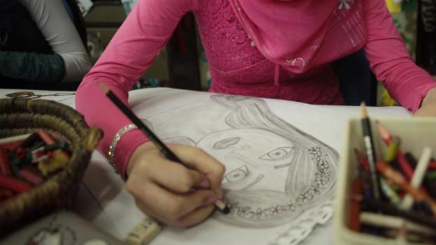Kind zeichnet Frau