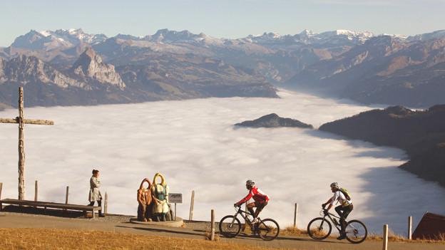 Velofahrer vor Nebelmeer und Bergen