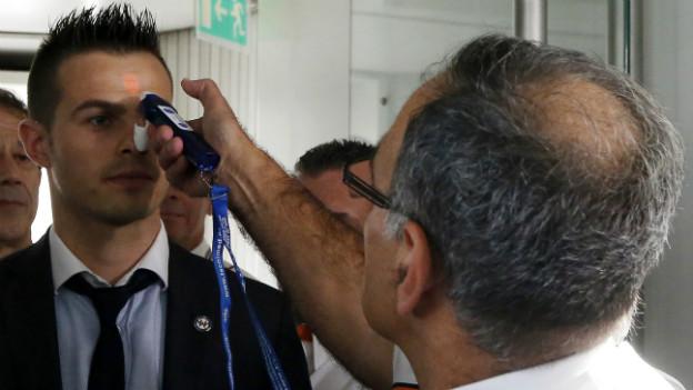 Ein Arzt misst die Temperatur an der Stirn eines Flugpassagiers.