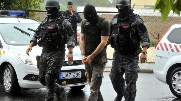 Vermummte Polizisten führen vermummten Mann ab.