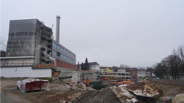 Links ein graues Industriegebäude, dahinter ein Kamin, rechts Baumaschinen und Schutt.