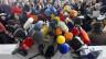 Auf dem Bild sind Mikrofone zu sehen, von verschiedenen Medienunternehmen, im Hintergrund sind Menschen zu sehen.