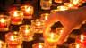 Mehrer Rechaud-Kerzen und eine Hand.